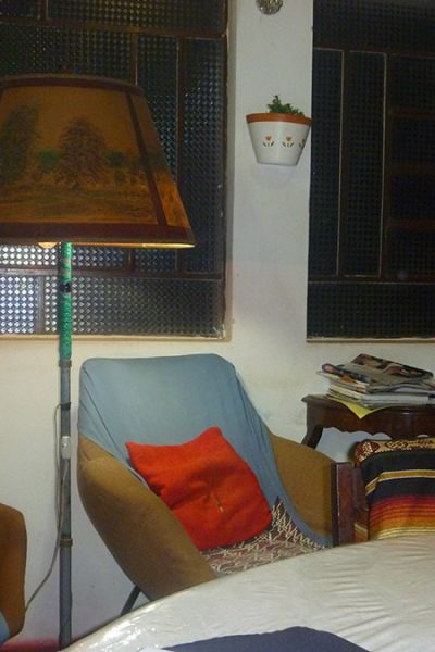 Cantinho de leitura. O abajur veio da Áustria, vê-se na cúpula o desenho característico. Ela sentava sempre na poltrona de almofada vermelha.